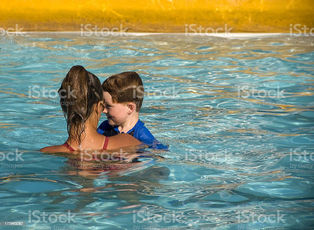 Child Learning to Swim, Boy Swimming with Caring Instructor stock photo