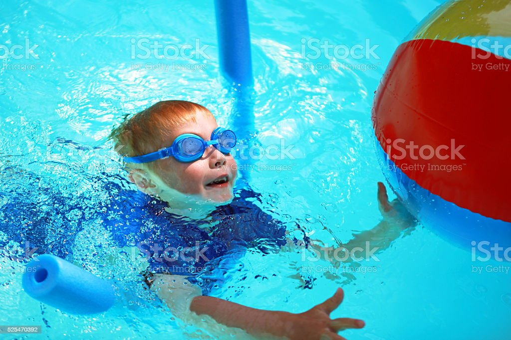 Child Learning to Swim in Outdoor Swimming Pool in Summer stock photo