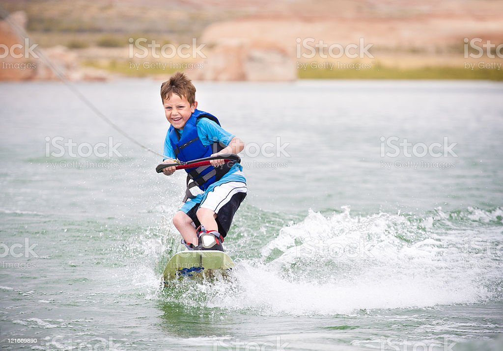 Child learning to wakeboard stock photo
