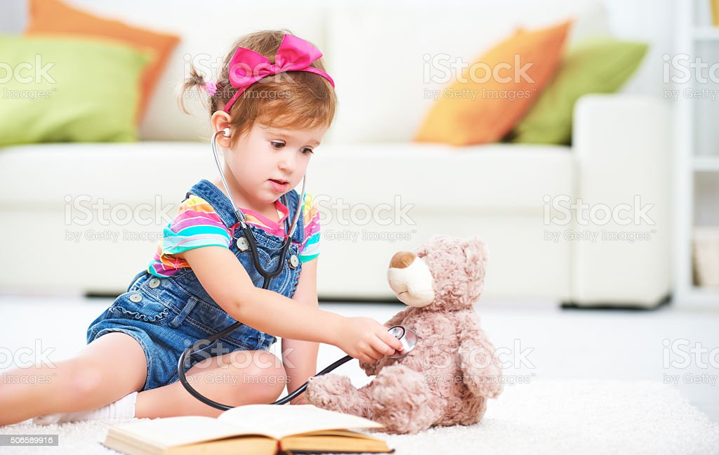 Child little girl playing doctor stock photo