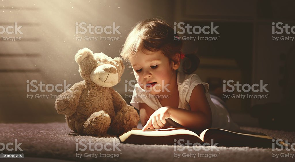 child little girl reading a magic book in the dark home with a toy...