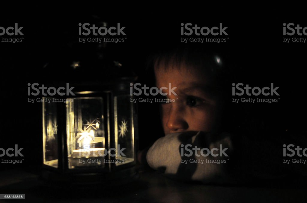 Child looking at candle light in lantern, high iso stock photo