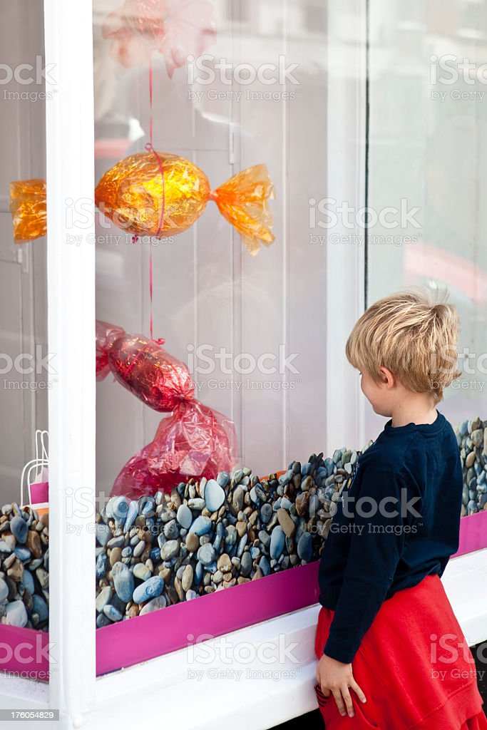 child looking at giant sweets in candy shop window royalty-free stock photo