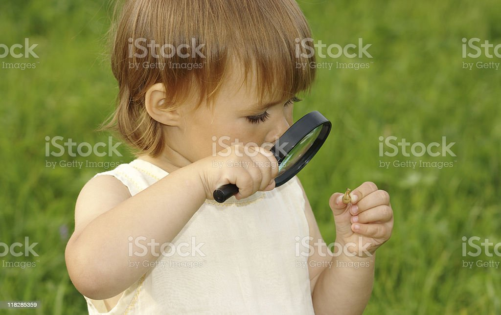 Child looking at snail through magnifying glass royalty-free stock photo