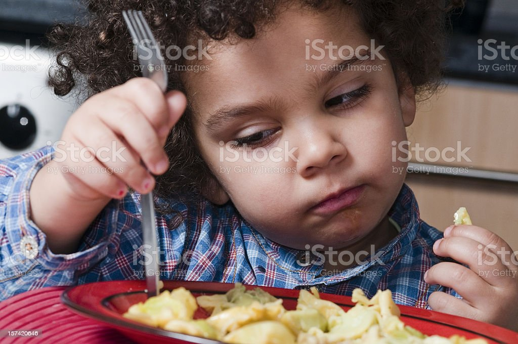 Child looking bored with her plate royalty-free stock photo