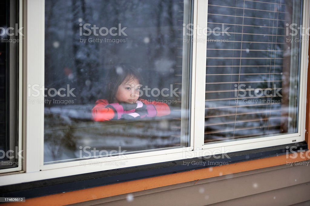 Child looking out of a window into a snowy scene royalty-free stock photo