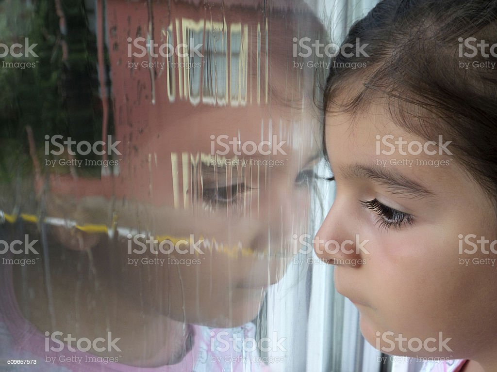 Child looking out window stock photo