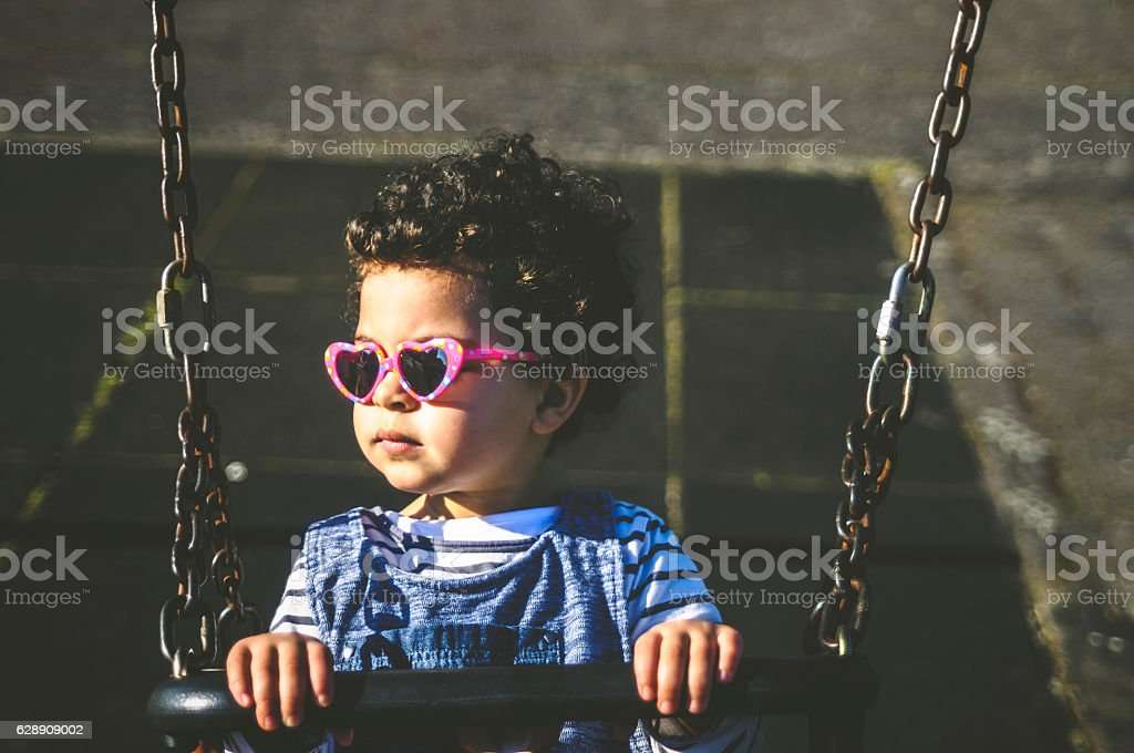 PEOPLE: Child (2-3) Looking Pensive on Swing. stock photo