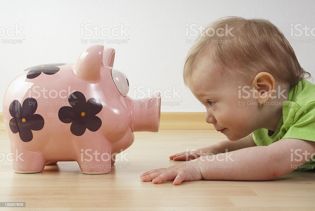 child looks at a piggy bank stock photo