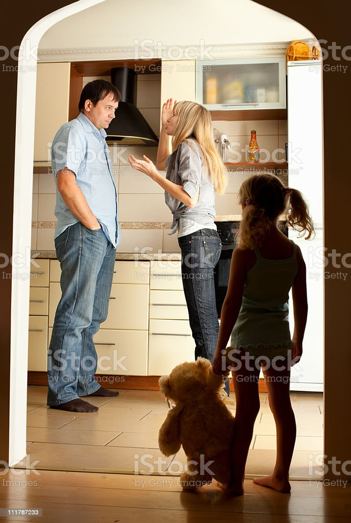 Child looks at the swearing parents stock photo