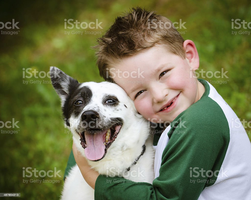 Child lovingly embraces his pet dog stock photo