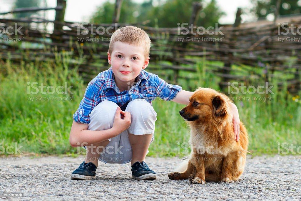Child lovingly embraces his pet dog. stock photo