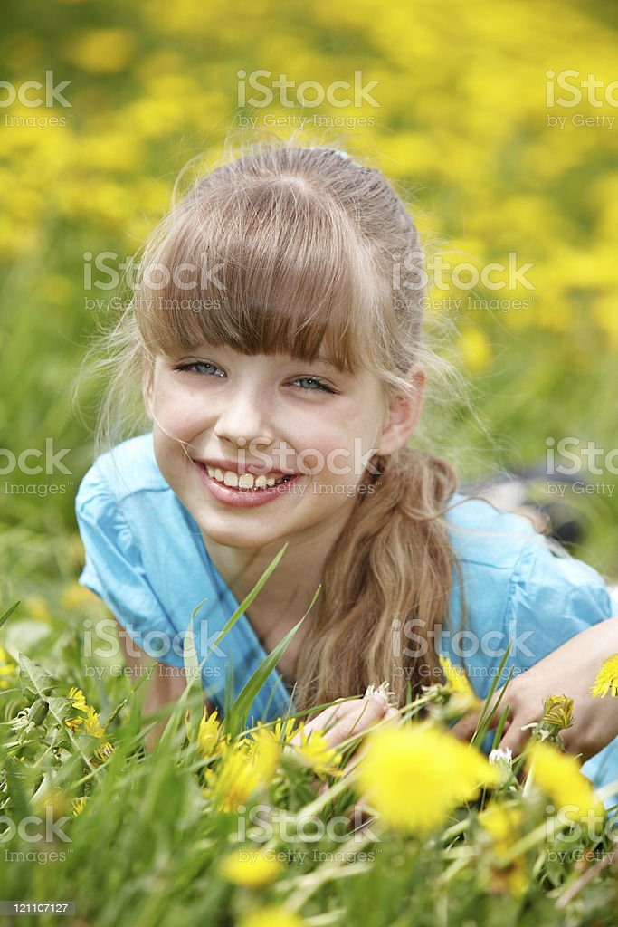 Child  lying on grass in flower. royalty-free stock photo