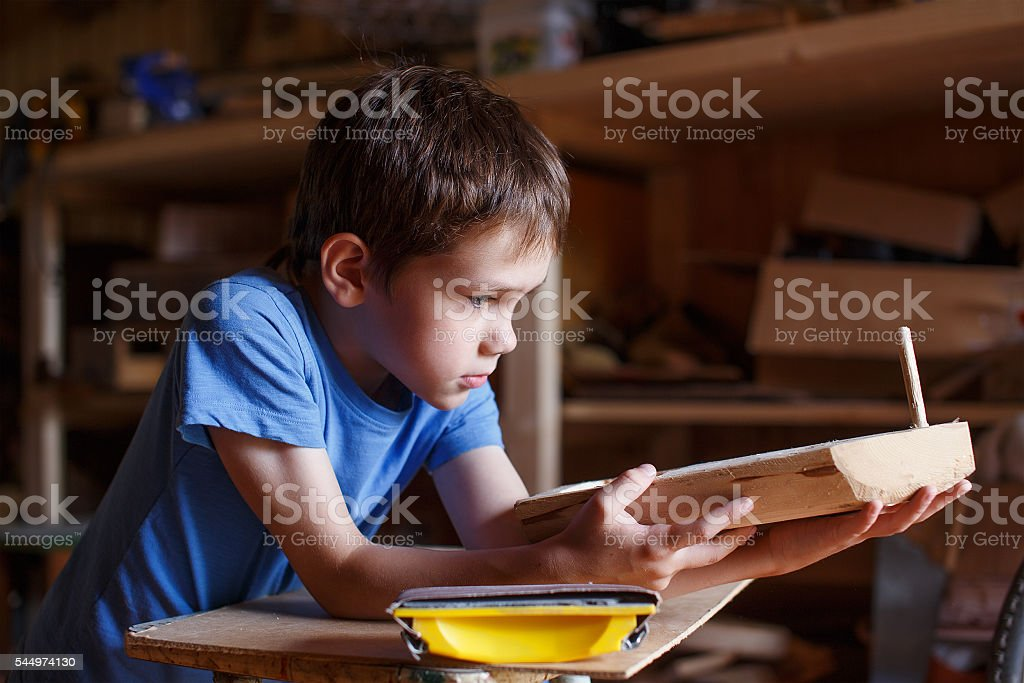 child makes a wooden ship stock photo