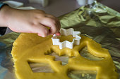 child makes dough cookie cutters