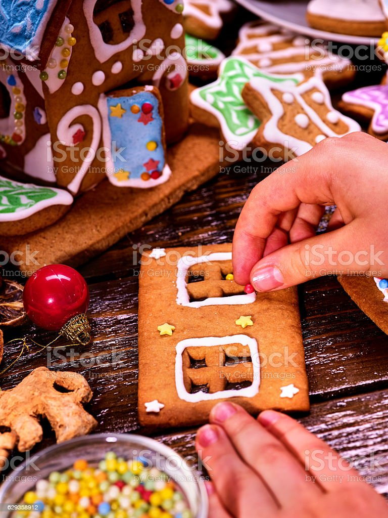 Child makes gingerbread house for Christmas. stock photo