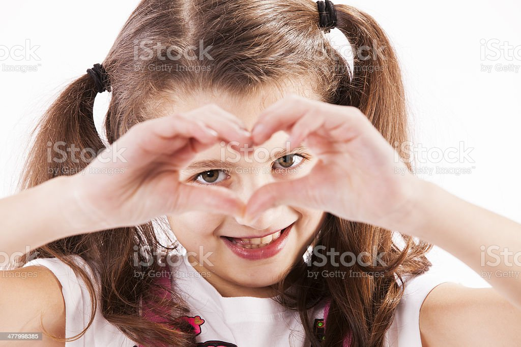 Child making a heart with her hands stock photo
