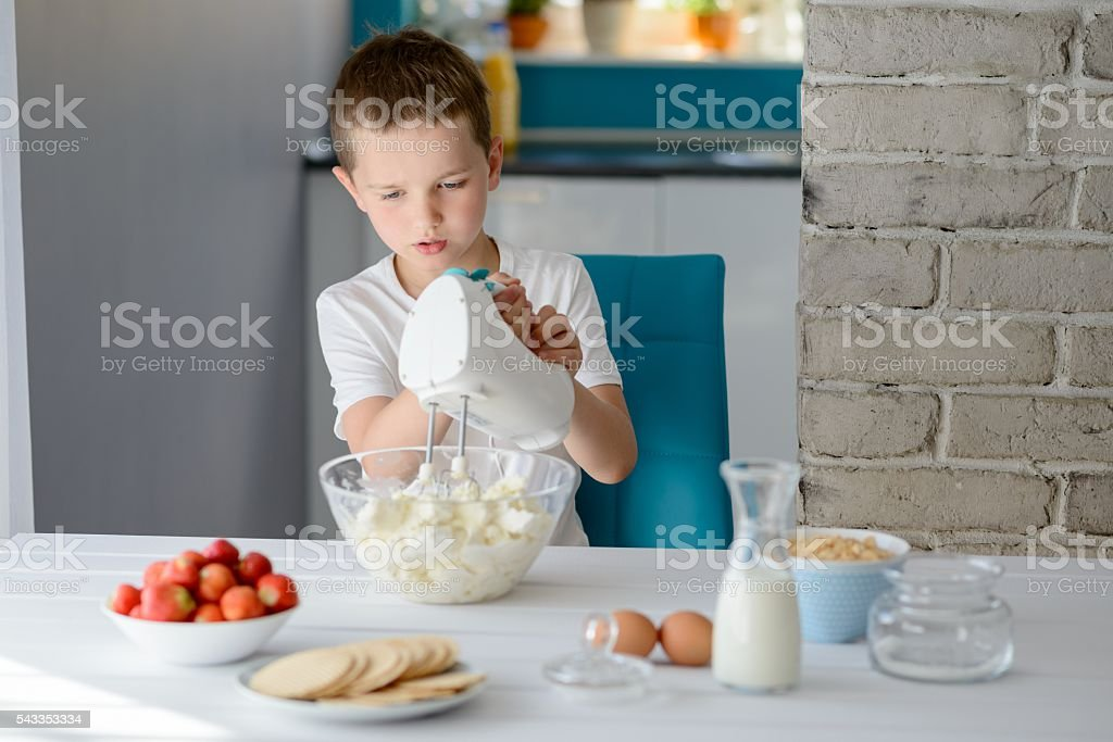 Child mixing with electric mixer white cottage cheese stock photo