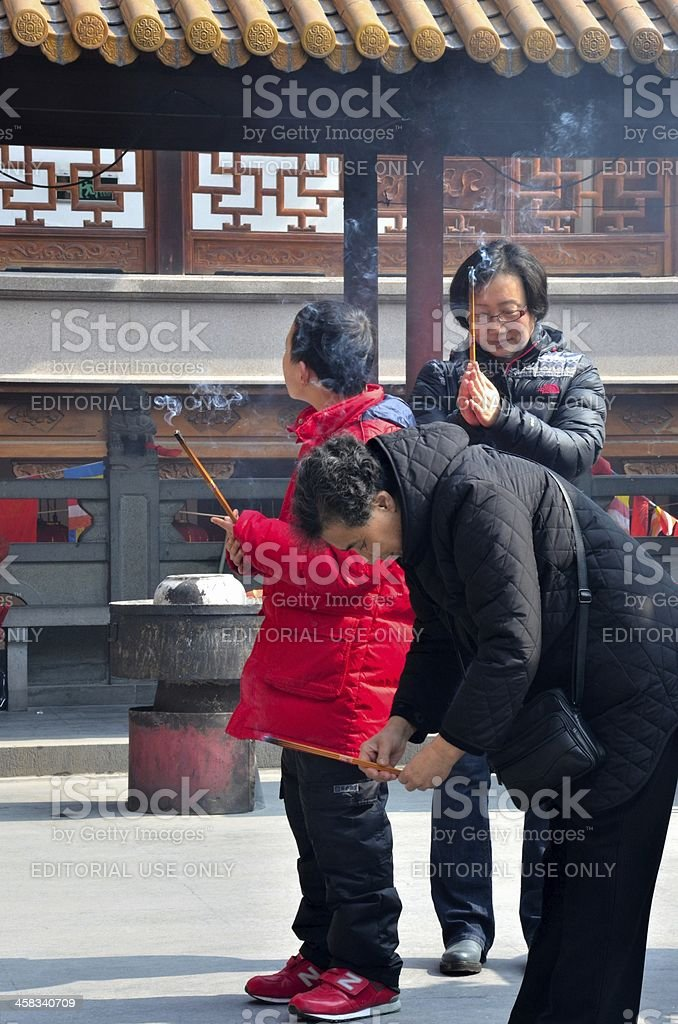Child, mother and grandmother burn incense at temple: Shanghai, China royalty-free stock photo