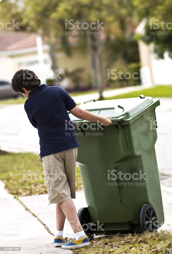 Child moving a wheeled trash can royalty-free stock photo
