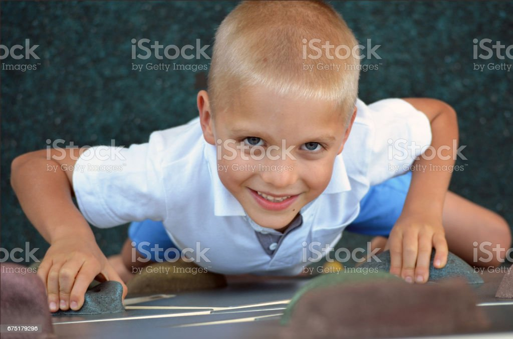 Child on a climbing wall in a park stock photo