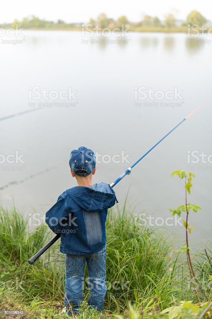 child on a summer fishing on the shore stock photo