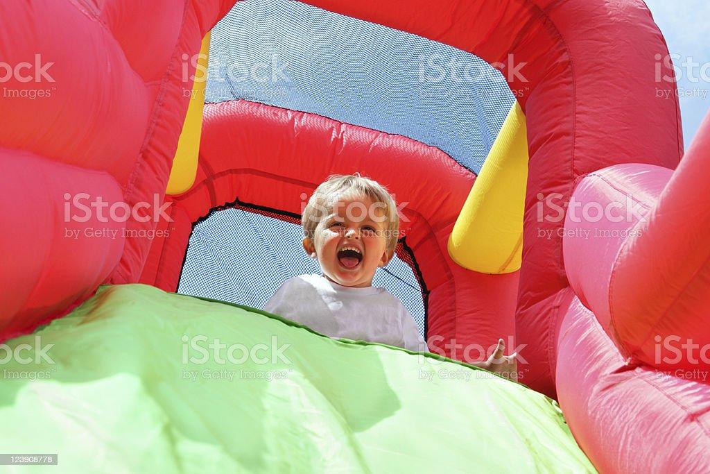 Child on bouncy castle slide stock photo