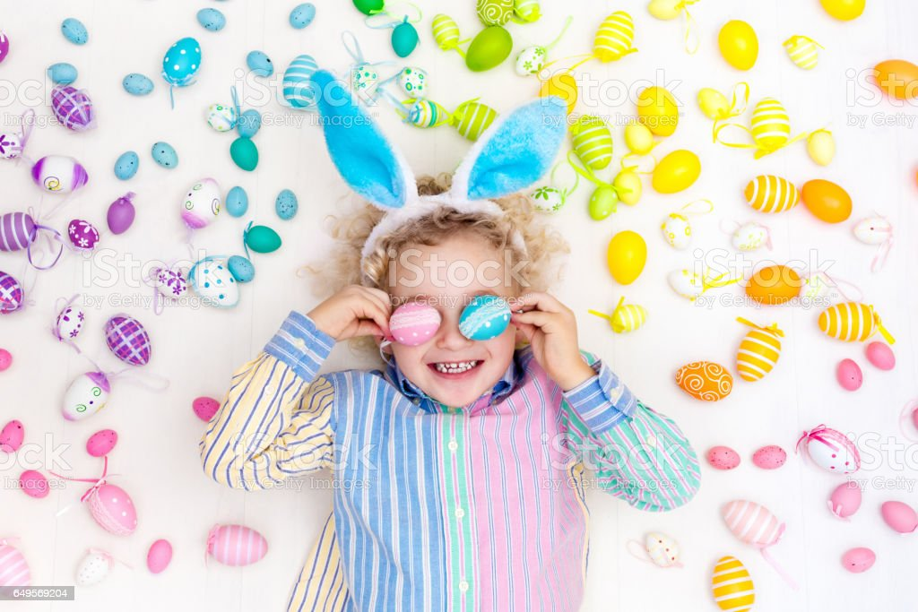 Child on Easter egg hunt. Pastel rainbow eggs. stock photo