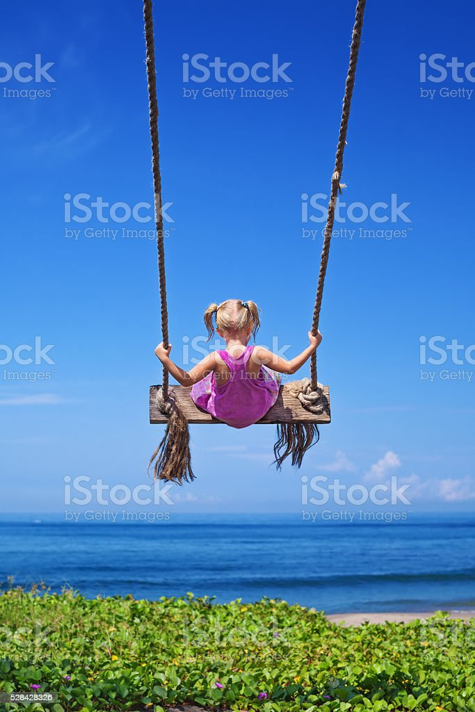 Child on flying high on rope swing on sea beach stock photo