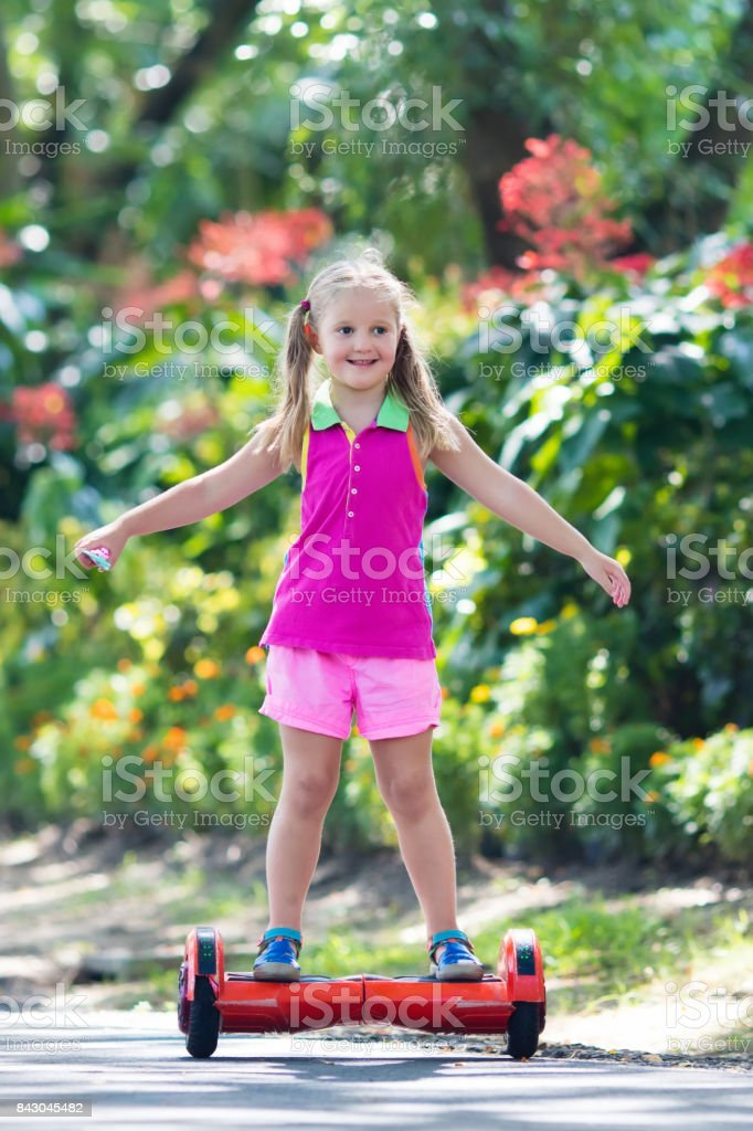 Child on hover board. Kids ride scooter. stock photo