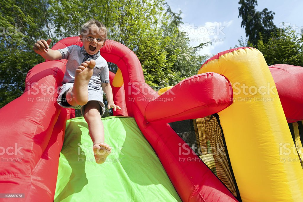 Child on inflatable bouncy castle slide stock photo