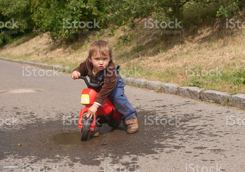 Child on motorbike in puddle stock photo