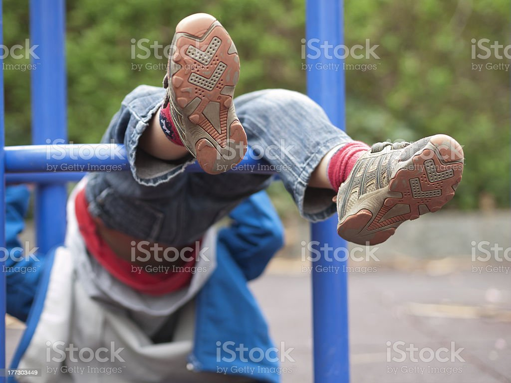 Child on playground swinging upside down, shoes in the air royalty-free stock photo