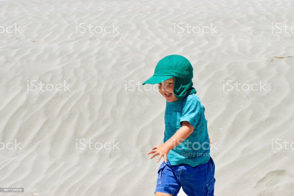 Child on Sand Dunes on the Beach stock photo