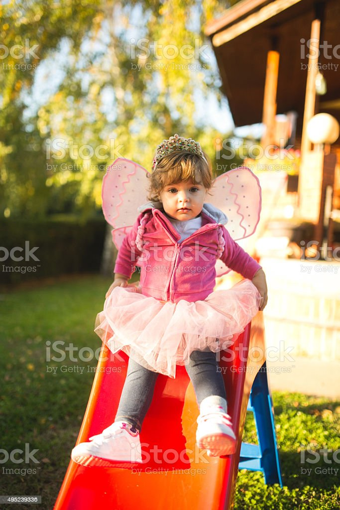 Child on slide in back yard stock photo