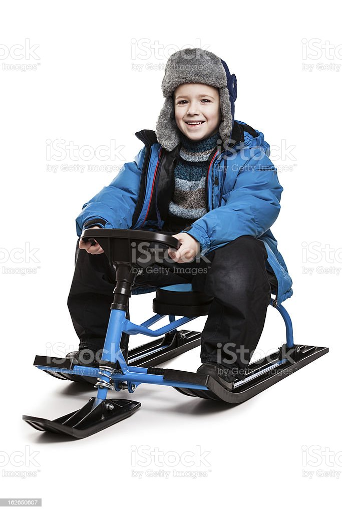 Child on snow scooter or snowmobile toy stock photo