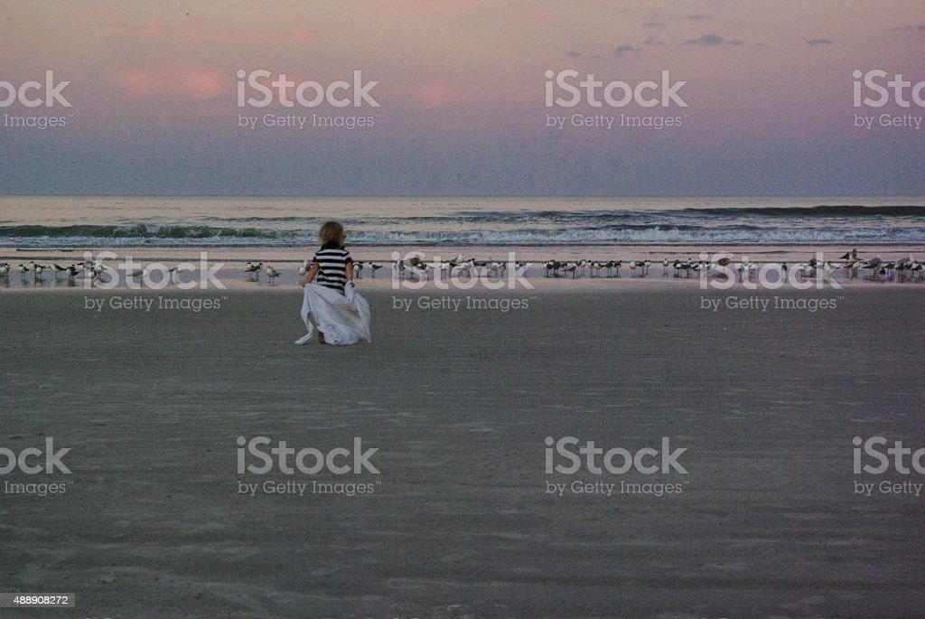 Child on the beach at sunset stock photo
