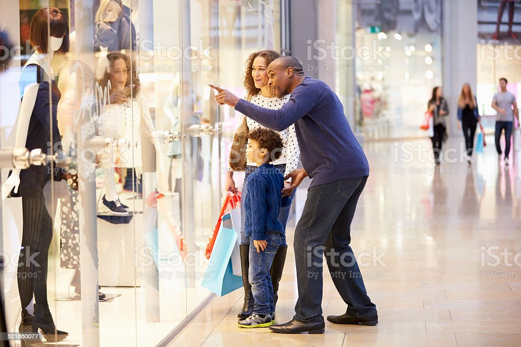 Child On Trip To Shopping Mall With Parents stock photo