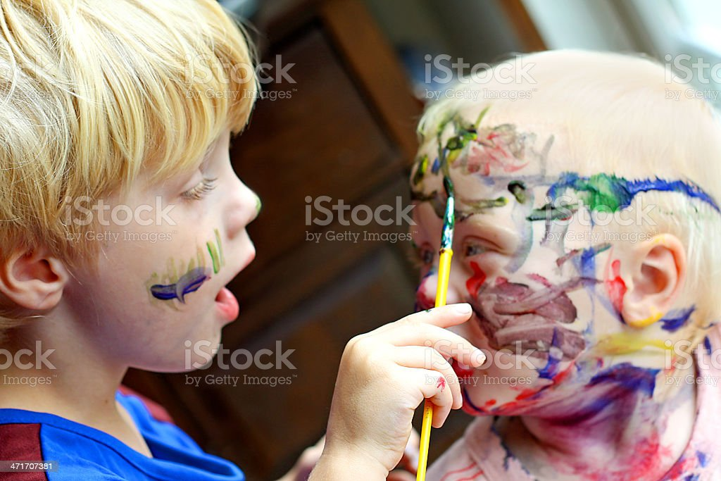 Child Painting his Baby Brother's Face stock photo