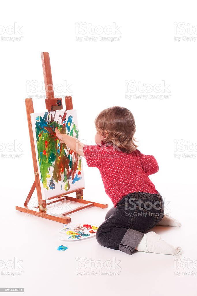 Child painting on easel with fingers stock photo