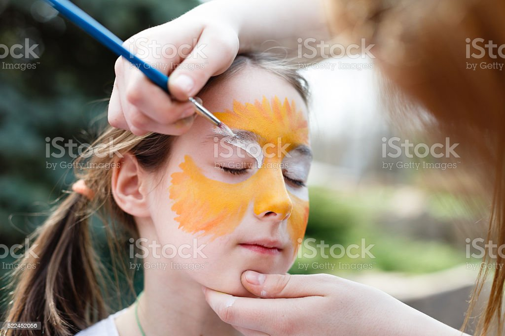 Child painting process at girl's face stock photo