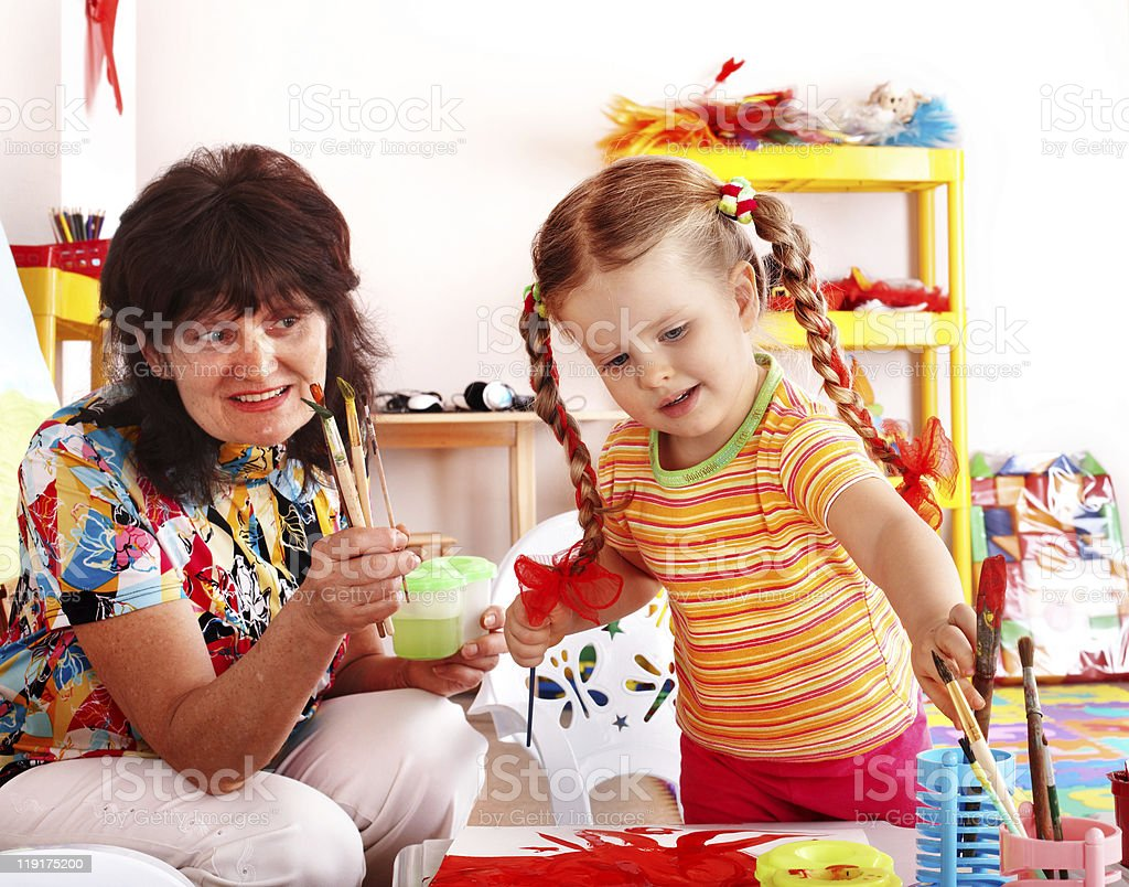 Child painting with teacher. royalty-free stock photo