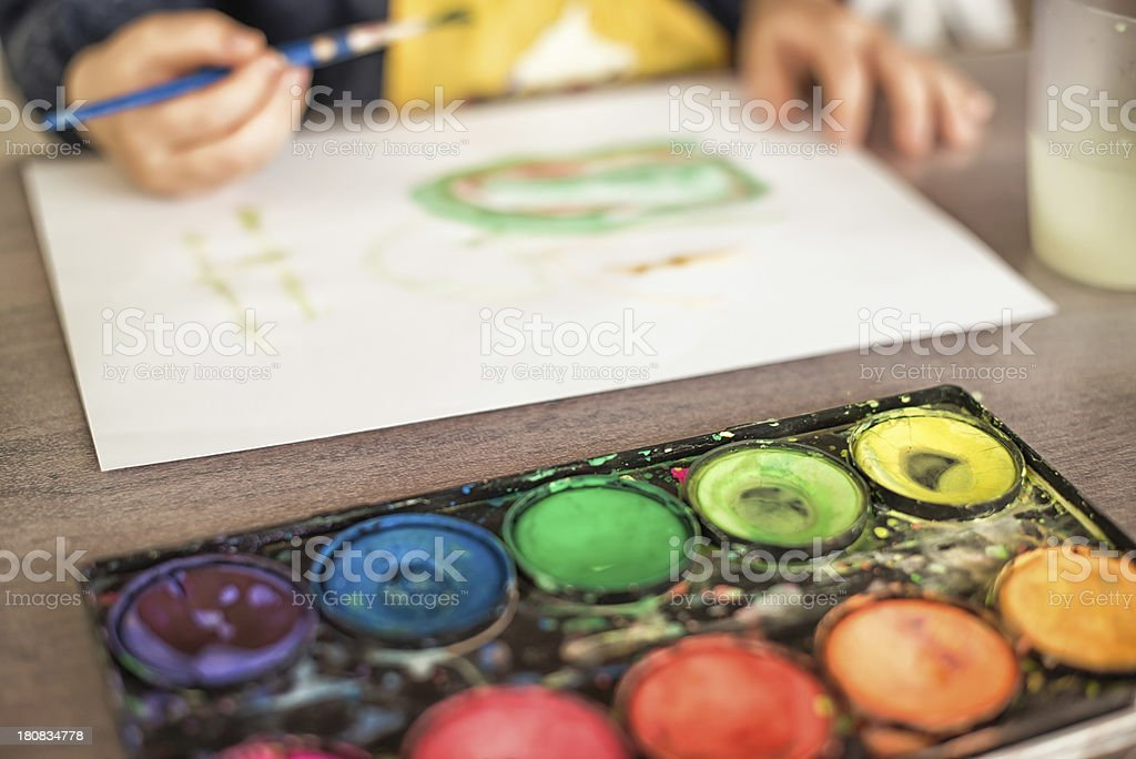 Child painting with watercolor rainbow colors royalty-free stock photo