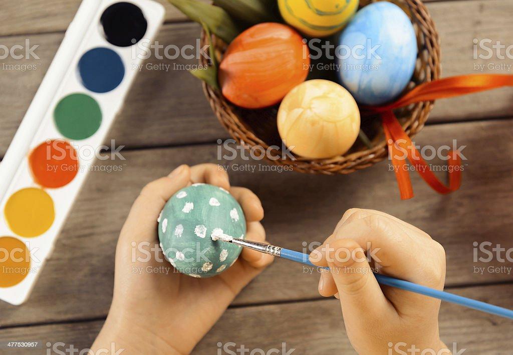Child paints egg for Easter, focus on eggs stock photo