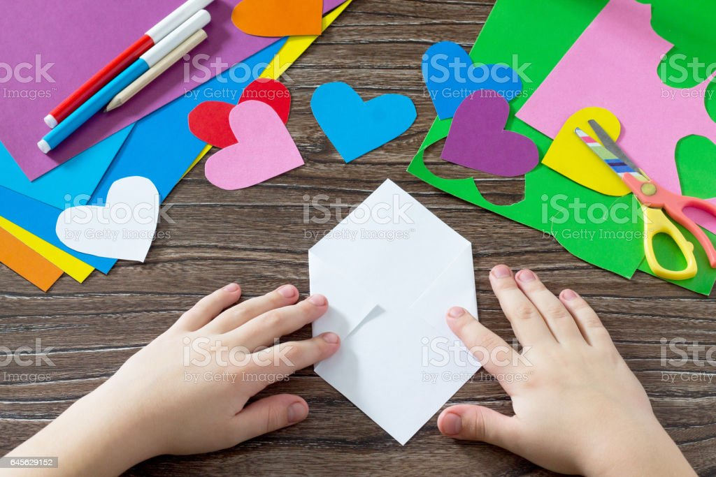 Child paper fold details. Greeting card with paper rainbow heart. Sheets of paper, glue and scissors on a wooden table. Children's art project, a craft for children. Craft for kids. stock photo