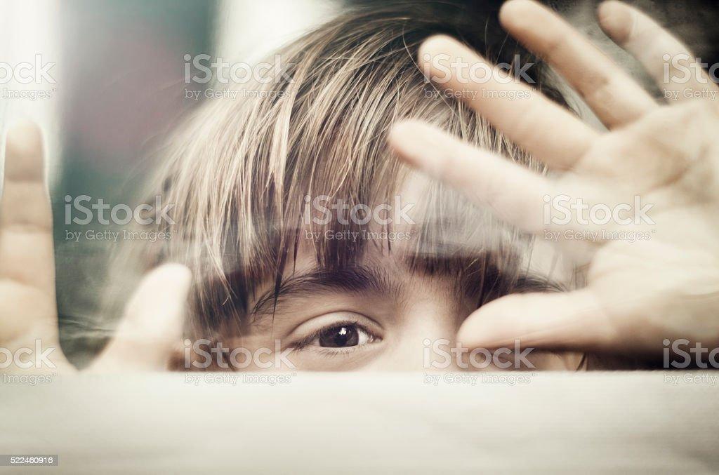 Child peeking through window stock photo