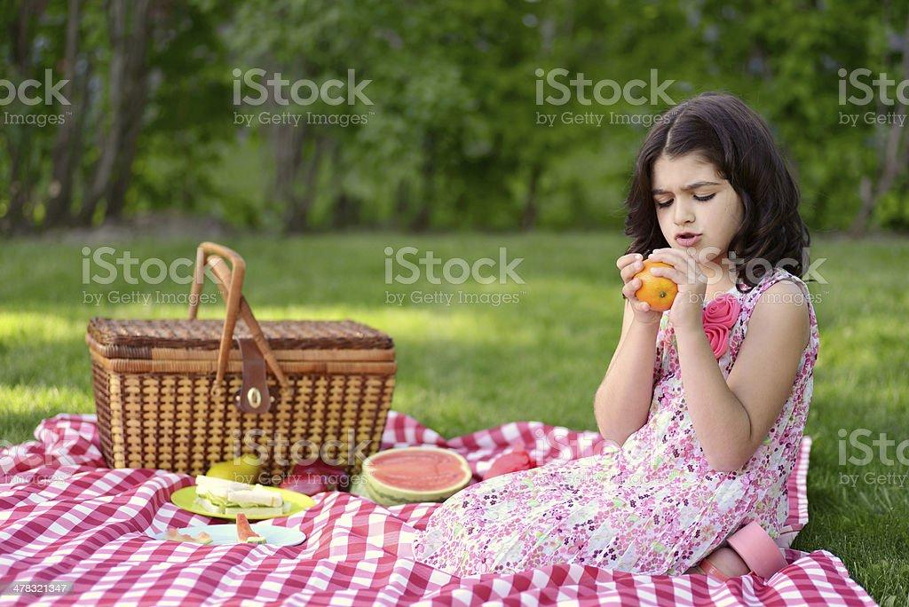 child peeling orange at picnic royalty-free stock photo