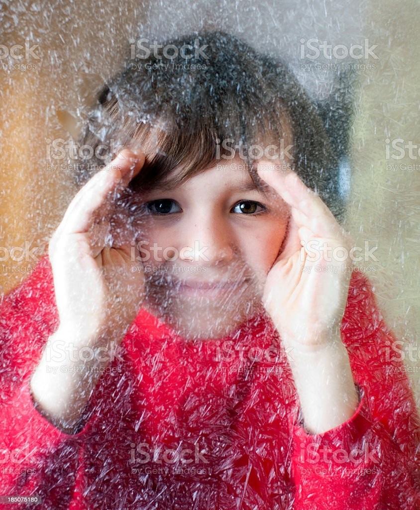 Child peering thru winter frosted window royalty-free stock photo