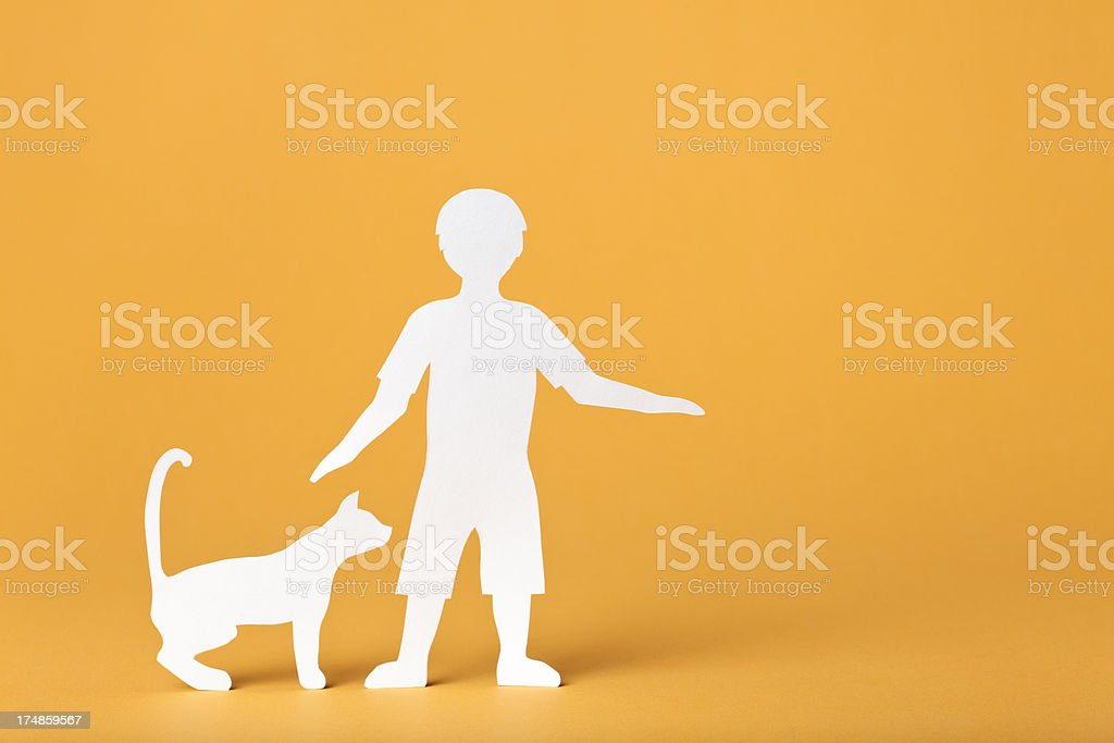 Child petting a cat: paper concept royalty-free stock photo