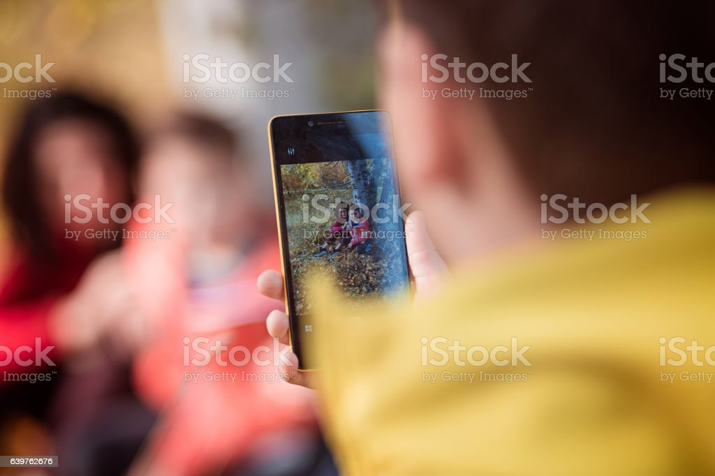 Child photographing mother on the phone stock photo